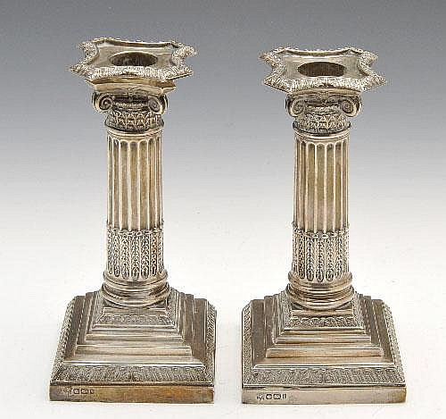 A pair of Edwardian silver mounted Corinthian column candlesticks.