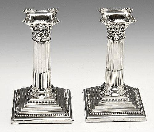 A pair of Edwardian silver mounted  candlesticks.