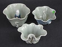 THREE CHINESE PORCELAIN CELADON GLAZED LOTUS LEAF FORM BRUSH WASHERS two of which have figural centr