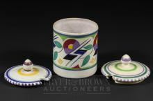A small Poole Pottery cylindrical pot, shape 286, abstract JV pattern, decorated by Myrtle Bond, 1927-42, 7.5cm high; together with two Poole Pottery pot lids (3)