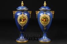 A pair of Royal Worcester vases & covers, signed E. Townsend, powder blue ground with reserves of fruit, shape no. 2713, date cipher for 1938, 20cm high approx. (2)