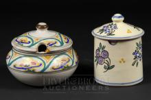 Two Honiton Pottery preserve pots & cover, one of cylindrical form decorated with blackcurrants and blue flowers, shape no. 13, the other of squat form decorated with a repeating border in green, yellow and blue, shape no. 15, both impressed Collard, Honiton, England (2)