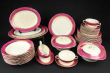 A Royal Cauldon part dinner service, gilt and rose pompadour borders, comprising seven dinner plates, twelve soup plates, twelve side plates, two soup bowls & stands, ten plates, two tureens & covers, gravy boat & stand, three meat platters in sizes (qty)