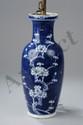 Vase balustre en porcelaine blanche décoré en réserve d'une branche de cerisier en fleurs sur fond bleu outremer à la base le double cercle en bleu sur fond blanc. Chine. Dynastie Qing. Période Kangxi. 1662 à 1722. Ht 30,5cm x diam 8,5cm.