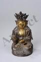 Buddha couronné assis en méditation d'une main marquant le geste de l
