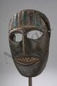 Masque anthropomorphe esquissant un sourire sur des dents en damier les yeux largement ouverts et coiffé d'une couronne simulée par des barrettes verticales polychromes. Bois à patine d'usage. Teraï. Népal. Ancien.