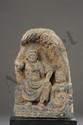Frise Bouddhique illustrant l'un Boddhisattva assis à l'européenne vêtu d'une robe monastique plissée accompagné d'un disciple à ses pieds, tout deux abrités sous une niche ciselée d'une branche d'arbre. Schiste gris. Art Greco Bouddhique du Gandhara