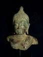 Buste de Buddha coiffé de fines bouclettes surmonté de la protubérance crânienne ushnisha terminé par un rasmi en bouton, les yeux mi-clos exprimant la sérénité. La robe utarasanga est rabattu sur l'épaule gauche par un pli arrêté au dessus de la