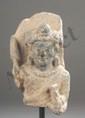 Buste de Boddhisattva auréolé d'un nimbe, paré d'un pectoral, vêtu de la robe monastique et coiffé d'une chevelure bouclée surmontée d'un haut chignon. Pierre Schiste gris. Art Gréco Bouddhique du Gandhara. Afghanistan. 2 ème à 3 ème siècle. 14 x 8