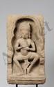 Fronton de sanctuaire illustré en haut relief d'une devata dansante, les mains posées sur sa poitrine marquant des mudras dans une niche à arcature polylobée, coiffée d'un diadème rehaussée de trois pétales, parée d'un pectoral et de lourds pendant