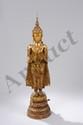 Buddha debout dans une posture hiératique sur un piédestal conique étagé, les deux mains en abaya mudra, geste du renoncement. Il est vêtu d'une robe monastique richement brodé et couronné d'une haute tiare orfévrée surmonté d'un important rasmi.