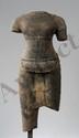 Torse de Shiva dans une posture hiératique paré d'un pectoral de bracelets, vêtu d'un sampot long finement plissé à larges poches drapées sur la ceinture sous le nombril, à bords rabattus, et double chute en ancre. La partie dorsale présente la forme
