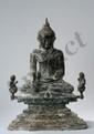 Buddha Maravijaya assis sur un haut socle étagé, deux petits donateurs agenouillés les mains jointes en adoration de part et d'autre. La main droite touche la terre à témoin et la gauche posée à plat dans son giron sur sa robe monastique lui couvrant