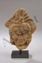 Tête de Shiva provenant d'un haut relief de sanctuaire illustrant la divinité de la trilogie hindoue coiffé du chignon d'ascète noué, symbolisant la source du gange, paré de lourd pendant d'oreilles et marqué du sourire typique khmer. Pierre grès