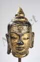 Tête de Buddha coiffé d'un important rasmi piriforme  sur son bulbe crânien ushnisha symbole de sa connaissance. Pierre laquée et dorée. Royaume de Pagan. Birmanie. 17 ème siècle. 26cm. Cassure à la pointe et au lobe d'une oreille.