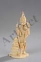 Vishnu debout sous une forme à quatre bras coiffé d'une haute tiare et accompagné d'un attendant assis en lotus. Ivoire fait au Japon pour l'Inde. 19 ème siècle.  18cm.