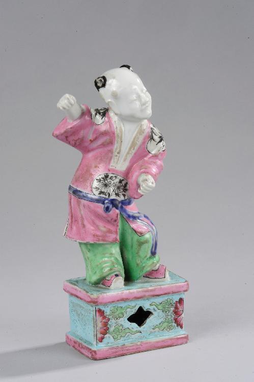 L'enfant symbolisant l'harmonie porteur de bonne fortune figuré debout sur un tertre quadrangulaire dans une attitude déhanchée vêtu d'une tunique ceinturée à la taille retombant sur un pantalon en porcelaine de la famille rose. Chine. Dynastie Qing.