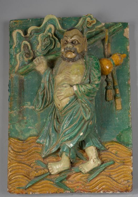 Important panneau murale de pagode sculpté en haut relief d'un Lohan, l'un des huit immortels. Céramique à glaçure bicolore verte et jaune. Chine. Dynastie Ming. 1368 à 1644. 57x40cm