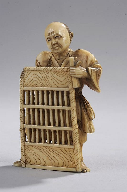 Okimono illustrant un ébéniste tenant une paroi de maison ajourée.  Ivoire. Japon. Période Edo. 19 ème siècle.  Ht 8cm.