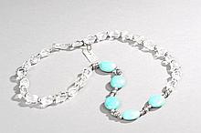 Collier recomposé selon la tradition de perles de cristal de roche, turquoise et métal argenté. Laddak.