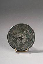 Miroir circulaire moulé d'un décor de motifs archaïsants autour d'une bossette  de préhension perçée sur une face l'autre face polie servait de miroir.  Chine.  Dynastie des Han.  206 avant à 220 après JC.  Diam 11,5cm.