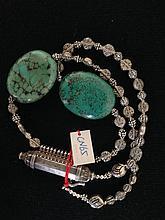 Collier recomposé selon la tradition de perles de turquoise, métal argenté terminé par un talisman.  Tibet.