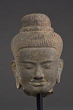 Tête de Shiva à la beauté juvénile coiffée de fines bouclettes organisées en tresses terminées par un chignon retenu par un anneau de perles.
