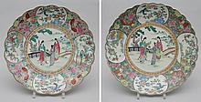 Suite de deux plats à marli polylobé en porcelaine de la famille rose décoré d'oiseaux de paradis et panier ikebana en réserve sur fond floral et papillon et d'une scène de palais au centre en émaux polychromes et rehaut d'or sur la couverte. Chine.