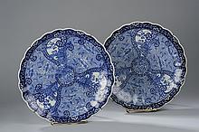 Paire de plats à marli polylobé en porcelaine blanche décorée en bleu de motifs floraux et rosaces de rinceaux. Japon. Période Edo. 19 ème siècle. Diam 37cm.