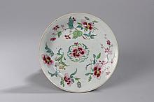 Assiette en porcelaine famille rose décorée de motifs floraux en émaux polychromes sur la couverte. Chine. Dynastie Qing. 18 ème siècle. 22cm.