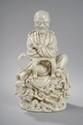 Lohan figuré assis vêtu de la robe monastique en porcelaine dites blanc de chine de Dehua. Chine. Province du Fujuan. Dynastie Qing.  32x19cm.