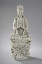 Le Boddhisattva Kwan Yin assis en vajrasana sur un haut tertre lotiforme vêtu de la robe monastique et coiffé d'un diadème en porcelaine blanc de Chine de Dehua. Province du Fujuan. Chine. Dynastie Qing. Fin 19 ème siècle. Ht   44cm.