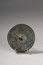 Miroir circulaire moulé d'un décor de motifs archaïsants autour d'une bossette  de préhension percée sur une face l'autre face polie servait de miroir. Chine. Dynastie des Han. 206 avant à 220 après JC. Diam 11,5cm.