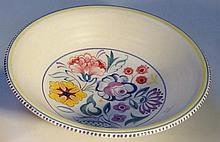 A Poole bowl, decorated with flowers in colours,