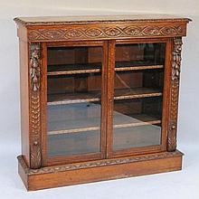 A Victorian oak freestanding bookcase, the carved