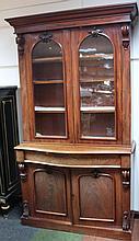 A Victorian mahogany serpentine bookcase, the upp