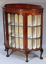 A 1920's mahogany display cabinet, of D-end form with a fixed cornice and a moulded outline, the thr