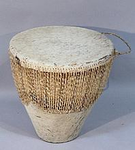 An African tribal drum, of circular tapering form with a hide skin top and part textured body, with