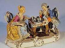 A Continental porcelain figure group, of a lady and gentleman playing chess, each dressed in finery,