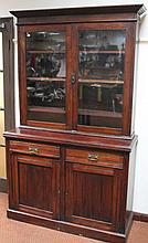 An Edwardian mahogany bookcase, the upper section with moulded cornice raised above two glazed doors