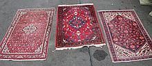 An Iranian rug, in geometric pattern predominately in red, cream and blue, 110cm wide, and two other