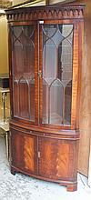 A Regency style mahogany finish freestanding corner cupboard, with a fixed dentil cornice raised abo