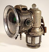 An early 20thC automobile light, with a circular glass front, the metal body with articulated parts,