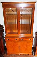 A yew finish bookcase, the upper section with a fixed cornice above two glazed doors revealing glass