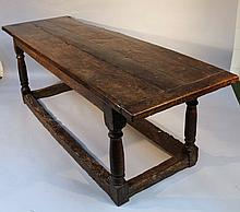 A principally 17thC oak refectory table, the plank top raised above a block frieze and turned suppor