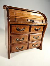 A miniature mahogany tambour fronted bow fronted cabinet, the cylindrical fall front above three dra