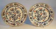 A pair of Continental earthenware plates, each of shaped circular form with gilt banding, each polyc