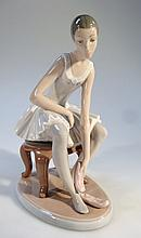 A Nao figure, of a ballerina seated changing her slippers in white, pink and brown, printed marks be