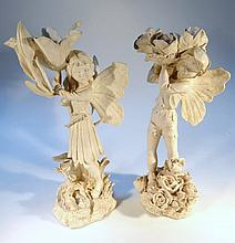 A pair of resin figures, of nymphs each standing holding flowers, on naturalistic bases, decorated i