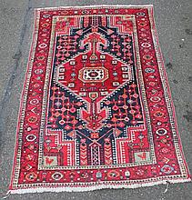An Iranian rug, of rectangular geometric pattern in red, blue and orange, 125cm x 93cm.
